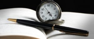 Pocket watch and pen resting across open book