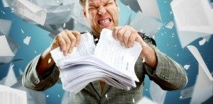 Frustrated man tearing stack of papers in half, with paperwork flying through air behind him
